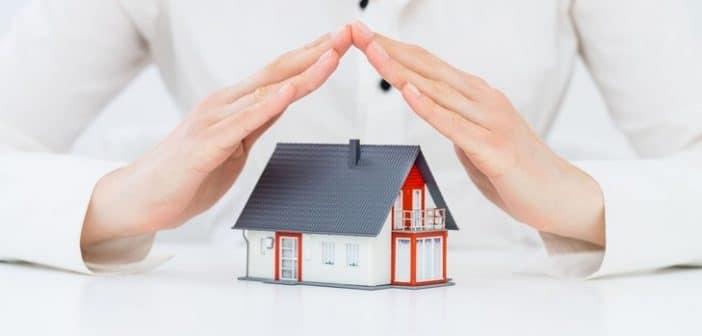 Une maison en jouet protégée par des mains