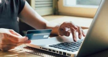 Un homme avec une carte de crédit devant son ordinateur
